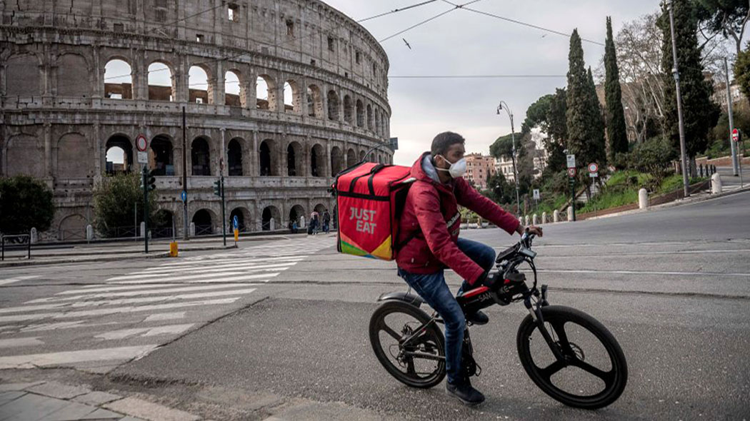 ROME, ITALY - MARCH 12: A delivery boy works near Colosseum area (Colosseo) during the Coronavirus emergency, on March 12, 2020, in Rome, Italy. The Italian Government has taken the unprecedented measure of a nationwide lockdown by closing all businesses except essential services such as, pharmacies, grocery stores, hardware stores and tobacconists and banks, in an effort to fight the world's second-most deadly coronavirus (COVID-19) outbreak outside of China. The movements in and out are allowed only for work and health reasons proven by a medical certificate. The number of confirmed cases of the Coronavirus COVID-19 disease in Italy has jumped up to at least 10590 while the death toll has surpassed 827. (Photo by Antonio Masiello/Getty Images)